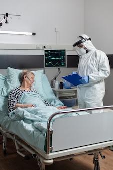 Paziente anziana che giace incosciente nel letto d'ospedale durante l'epidemia di coronavirus, respirando con l'aiuto della maschera di ossigeno