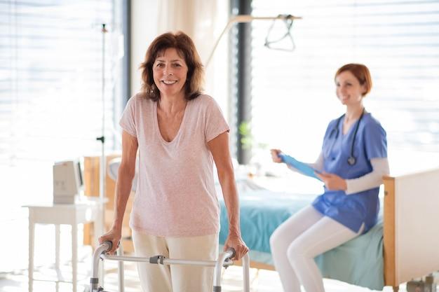 Una donna anziana paziente con deambulatore e infermiera nella stanza d'ospedale.