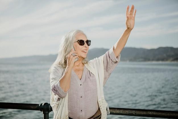 Donna anziana al telefono che saluta in riva al mare