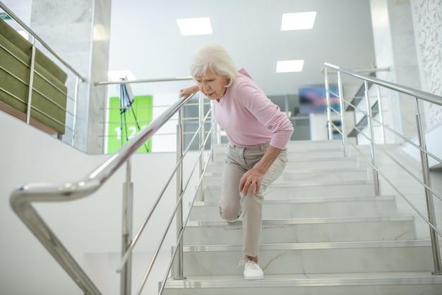 Senior donna in camicia rosa che cade sulle scale