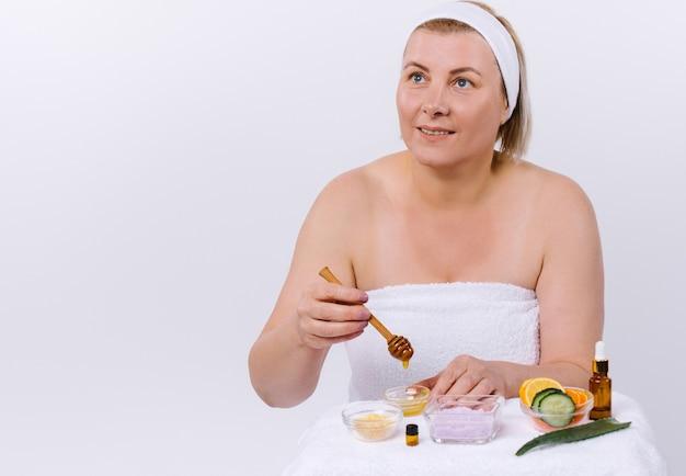 La donna senior prepara una maschera per il viso e il corpo da prodotti naturali a casa e distoglie lo sguardo. cura della pelle domestica. foto di alta qualità
