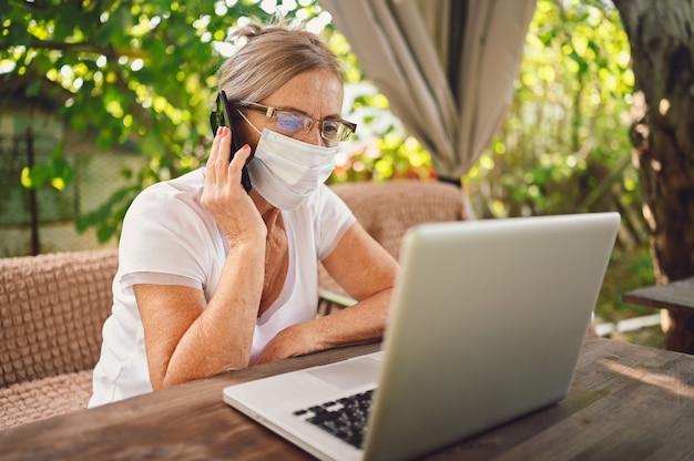 Senior donna in maschera protettiva utilizzando laptop