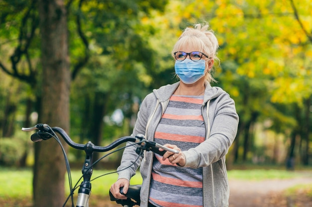 Donna senior in una maschera protettiva sul viso che cammina nel parco con una bicicletta