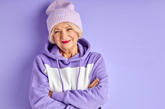Senior donna in pullover viola e cappello in posa, donna alla moda piace essere alla moda, guarda la telecamera con le braccia incrociate