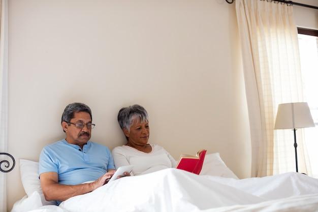 Donna senior che legge un romanzo e un uomo senior che per mezzo della compressa digitale sul letto