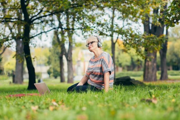 Senior donna rilassante nel parco con un computer portatile
