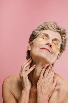 Donna anziana che si rilassa con una maschera per gli occhi dorata