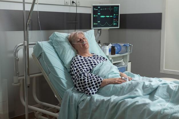 Donna anziana che riposa nel letto d'ospedale respirando con l'aiuto della maschera di ossigeno, a causa di una malattia polmonare. ottenere medicine per via endovenosa dalla sacca per fleboclisi durante la terapia di recupero.