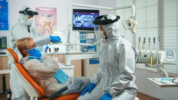 Donna anziana che mostra dente dolorante al dentista vestita in tuta durante l'epidemia di coronavirus. assistente e medico dentista che parlano con il paziente che indossa tuta protettiva, visiera, maschera e guanti