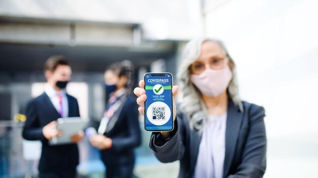 Donna anziana che mostra smartphone con covidpass, coronavirus, viaggi e nuovo concetto normale.