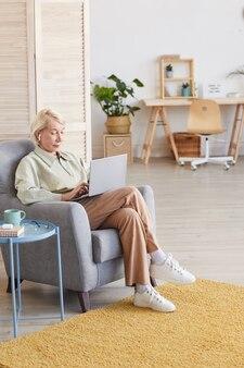 Senior donna seduta su una comoda poltrona e comunicare in linea utilizzando il suo laptop in camera