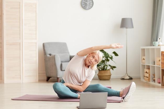 Senior donna seduta sul pavimento sulla stuoia di esercizio e allungando le mani mentre si guarda l'allenamento sportivo sul laptop a casa