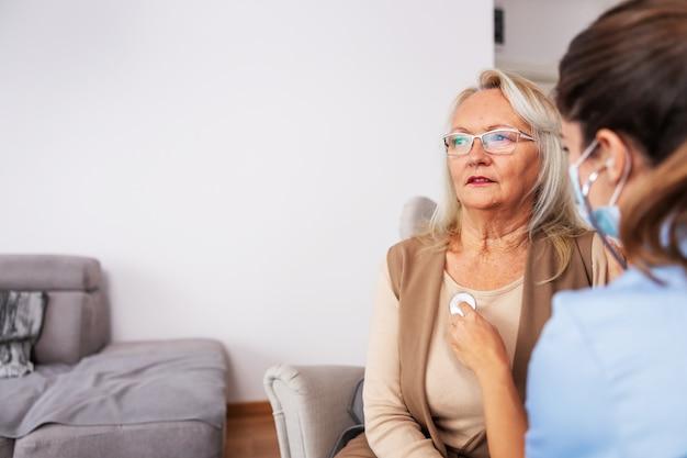 Senior donna seduta a casa e farsi controllare dall'infermiera. infermiera che tiene lo stetoscopio e ascolta i suoi polmoni.