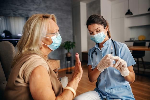 Senior donna seduta a casa e rifiutando di ottenere il vaccino per il virus corona. infermiera che spiega.