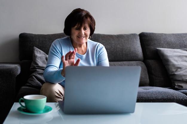 Senior donna seduta sul divano a casa un caffè durante la videoconferenza con il laptop