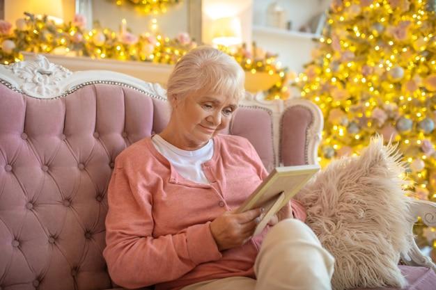 Senior donna seduta su un divano con una foto in mano