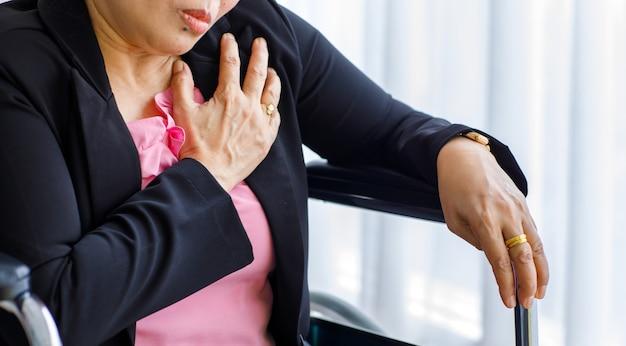 Senior donna seduta su sedia a rotelle che soffre di infarto improvviso e tenere il petto. concetto di assistenza sanitaria di emergenza e affetto da rianimazione cardiopolmonare, problema cardiaco.