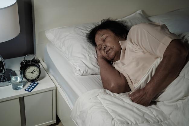 Donna senior che dorme in un letto di notte