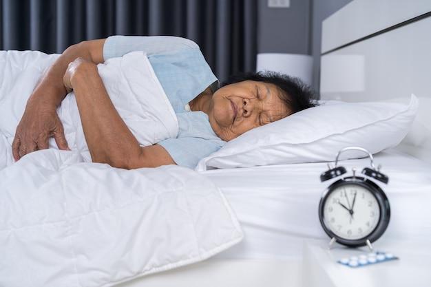 Donna senior che dorme su un letto con un orologio