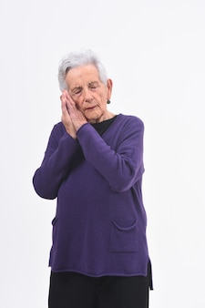 Senior donna che dorme sul bianco