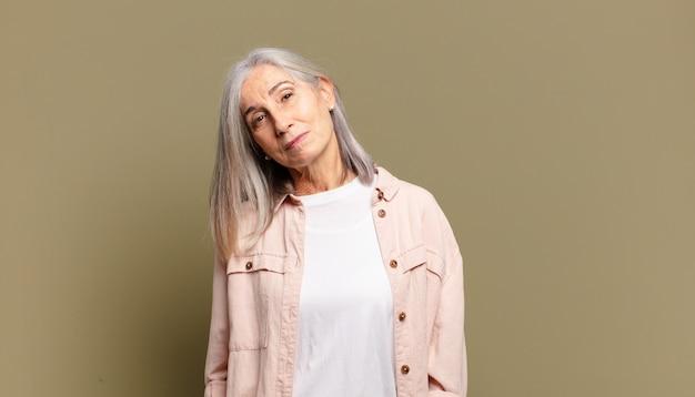 Donna anziana che sorride allegramente e casualmente con un'espressione positiva, felice, sicura e rilassata
