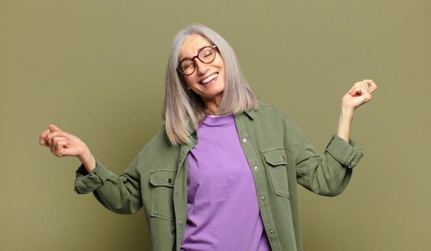 Senior donna sorridente, sentirsi spensierata, rilassata e felice, ballare e ascoltare musica, divertirsi a una festa