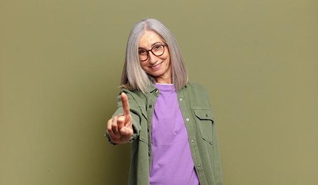 Senior donna che sorride con orgoglio e sicurezza facendo il numero uno posa trionfante, sentendosi come un leader