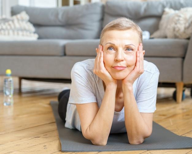 Donna anziana che sorride mentre si allena a casa