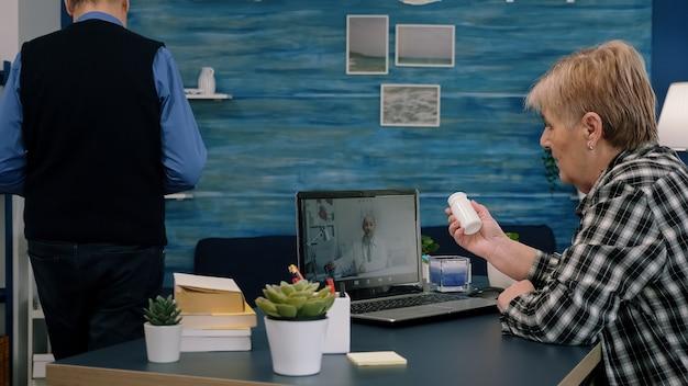 Donna anziana che parla online con il medico che si occupa del trattamento durante la telemedicina seduta a casa. signora malata che discute durante la consultazione virtuale sui sintomi che tengono il flacone di pillole