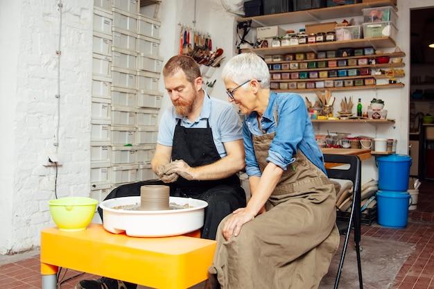 Argilla di filatura della donna senior su una ruota con l'insegnante alla classe delle terraglie