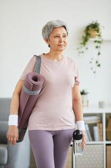Senior donna in abbigliamento sportivo e con stuoia di esercizio in piedi nella stanza domestica