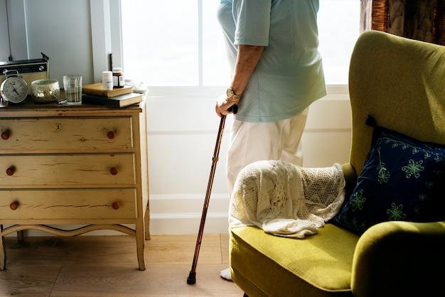 Donna senior che sta da solo nella stanza