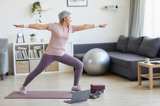 Senior donna in piedi sul tappetino esercizio durante l'allenamento sportivo nel soggiorno di casa