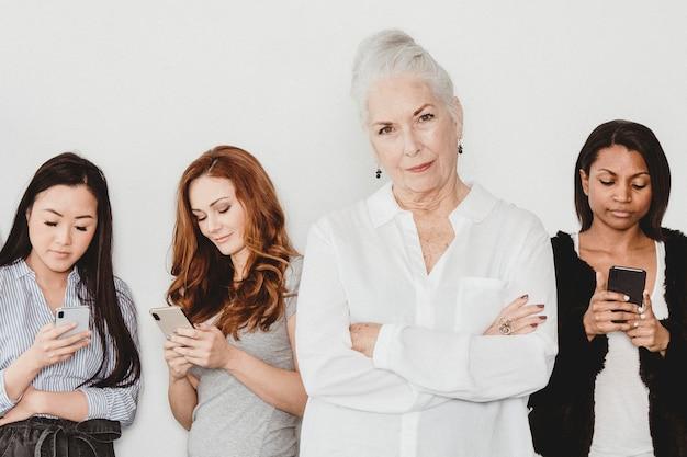 Senior donna in piedi di fronte a persone dipendenti dai social media