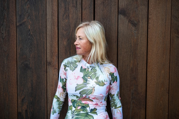 Una donna anziana in piedi all'aperto, in piedi su sfondo di legno. copia spazio.