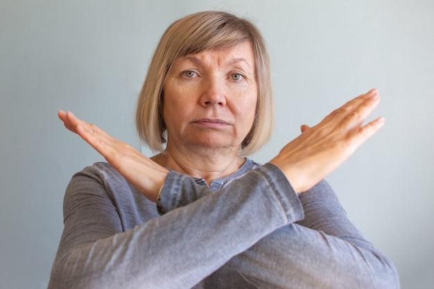 Donna anziana dipendente da stress e alcolismo da sola depressione, segnale di stop delle mani. mal di testa, vertigini, emicrania. concetti di documentario sociale.
