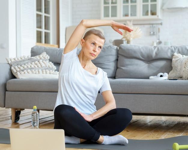 Senior donna stretching mano formazione online con laptop in soggiorno with