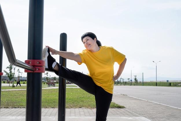 Senior donna che allunga le gambe all'aperto sul campo sportivo