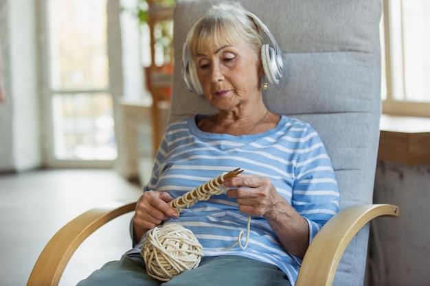 Donna anziana che studia a casa ricevendo corsi online