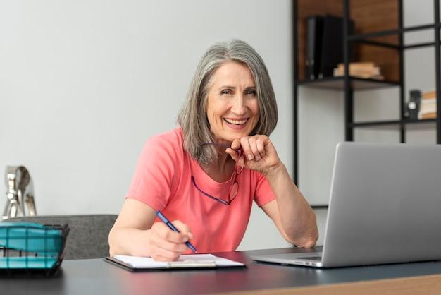 Donna anziana che studia a casa mentre usa il laptop e prende appunti