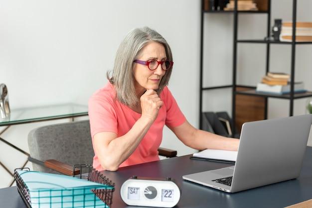 Donna anziana che studia a casa mentre usa il laptop Foto Premium