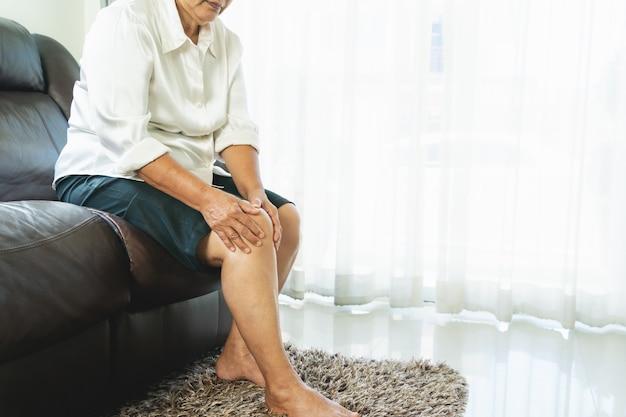 Donna anziana che soffre di dolore al ginocchio a casa, concetto di problema di salute