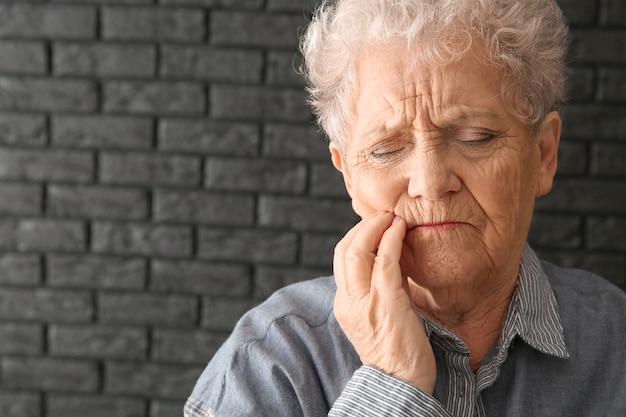 Senior donna che soffre di mal di denti su sfondo scuro