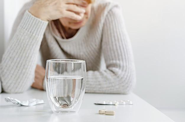 Donna senior che soffre e che prende le pillole dall'emicrania. concetto di trattamento mal di testa.