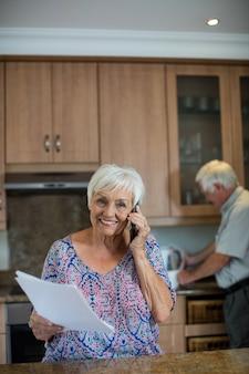 Senior donna parla al telefono cellulare mentre uomo che lavora in cucina a casa