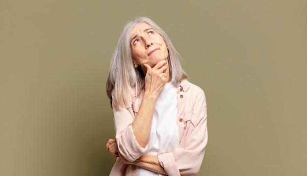 Senior donna pensando, sentendosi dubbioso e confuso, con diverse opzioni