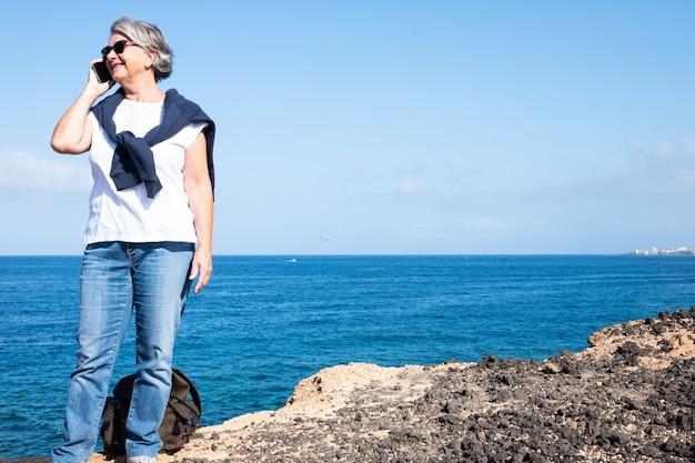 Donna anziana che utilizza il telefono cellulare in piedi sulla scogliera godendosi il tramonto e la pensione