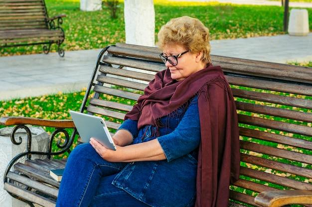 Senior donna che utilizza smartphone, leggere e-book, ridurre la musica o prendere lezioni online nel parco su una panchina