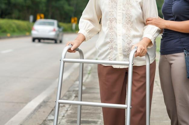 Senior donna utilizzando un deambulatore cross street