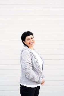 Senior donna waring giacca grigia in piedi all'aperto sul muro grigio solido